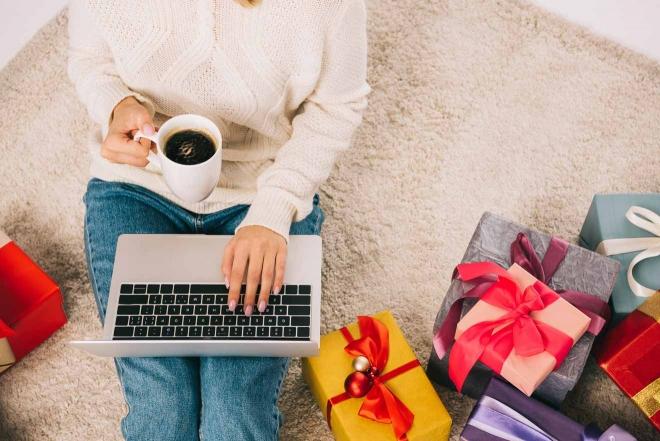 mujer con regalos café y laptop
